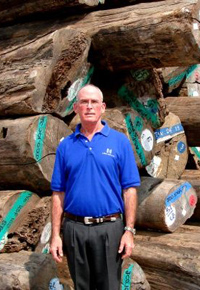 Gib McIlvain in front of Teak logs