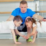 teacher instructing young gymnast boy and girl