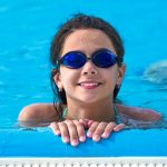 smiling young teen girl resting against pool edge