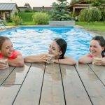 three girl friends rest at pool side drinking
