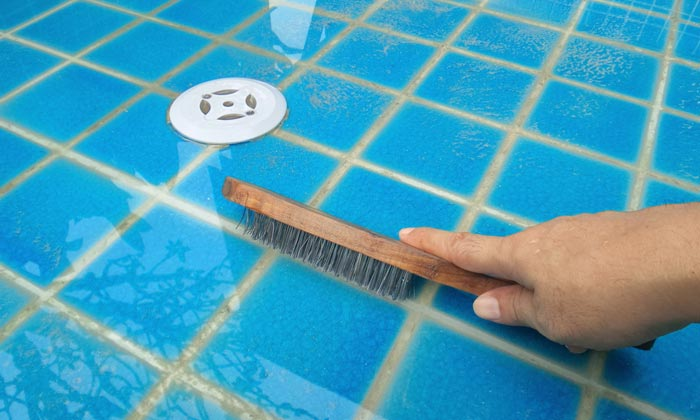 scrubbing pool floor tiles with brush
