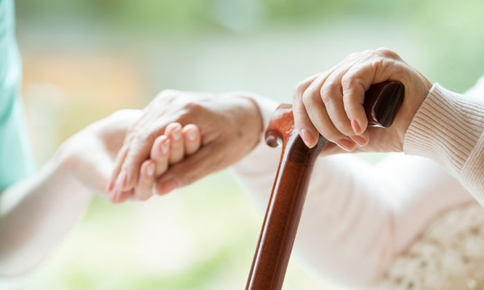 elderly woman with cane holding young womans hand