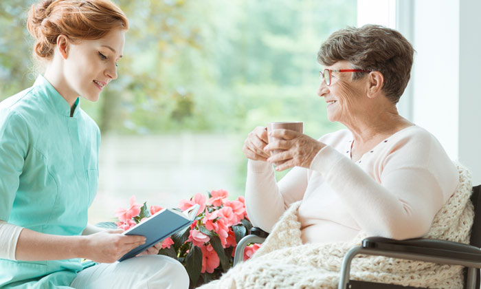 home caregiver reading book aloud to elderly lady