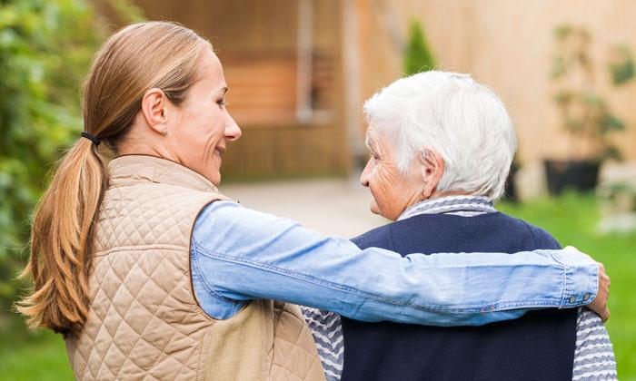 woman embracing elderly lady