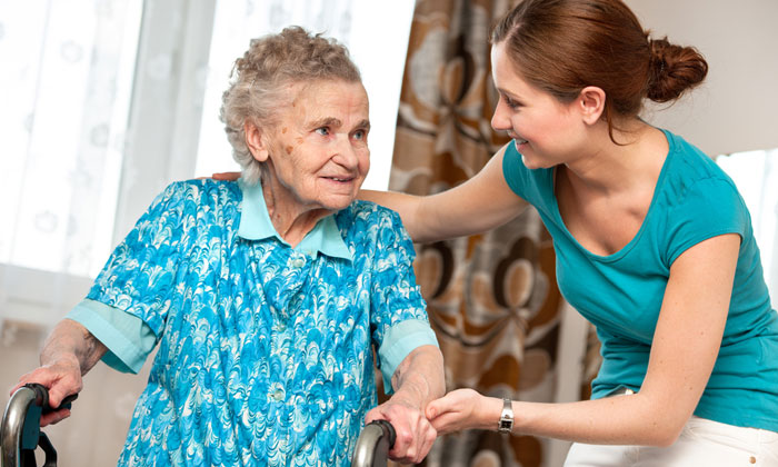 young lady helping senior citizen lady with walker