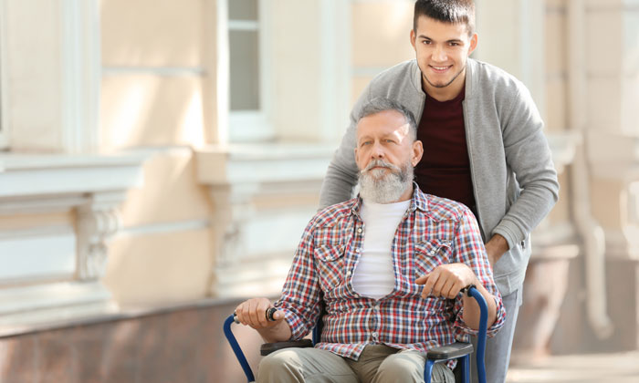 young male caregiver assisting elderly man in wheelchair