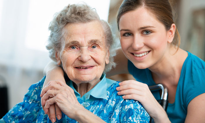 young pretty woman helping elderly lady