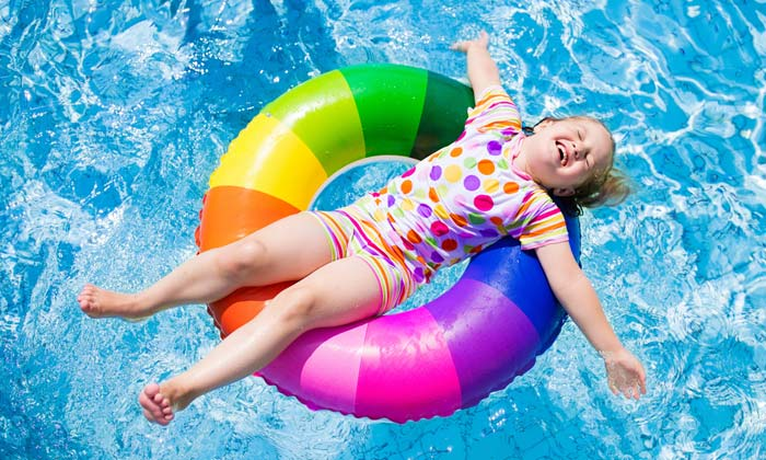 young girl relaxing arms spread on water tube