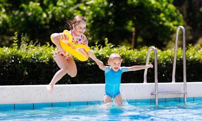 young siblings jumping into swimming pool excitedly