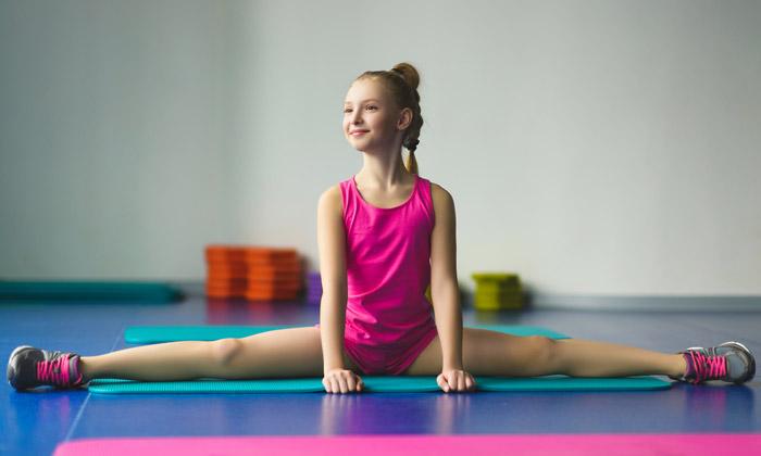 preteen girl doing leg stretch on gymnastic mat