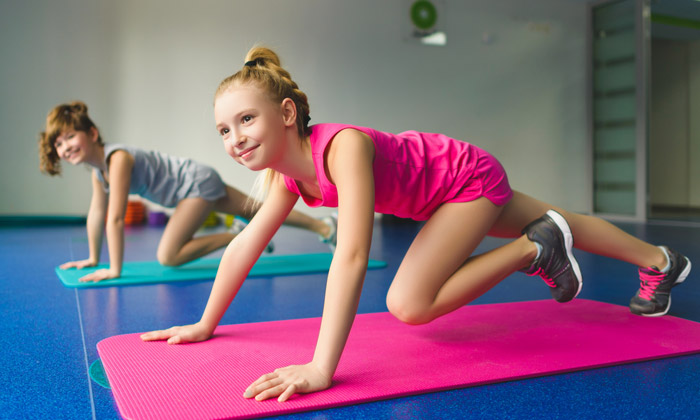 two teen girls practicing gymnastics on mats