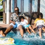 father and two kids kicking splashing water