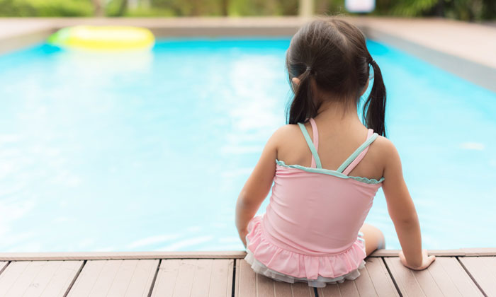 little girl sitting unsupervised at edge of swimming pool