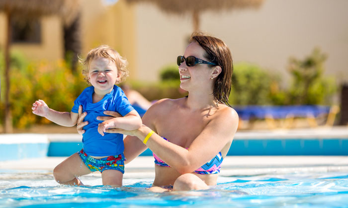 mother easing toddler into water of pool