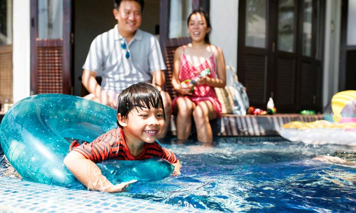 parents watching while child plays on inner tube in pool