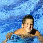 elementary age boy grimacing at cold pool water