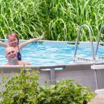 father and daughter excited in backyard pool