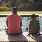 father and son sitting beside outdoor swimming pool