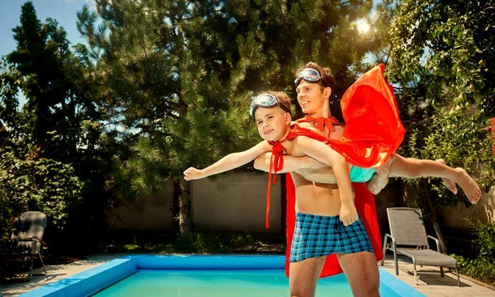 father helping superhero son fly beside pool