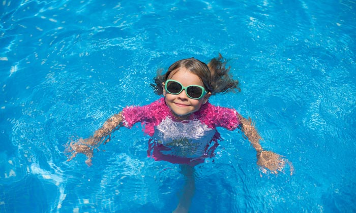 green sunglasses young girl smiling from pool