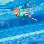 happy young child swimming effortlessly underwater