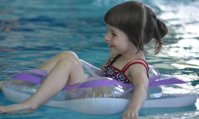 kindergarten girl floating on pool water and smiling