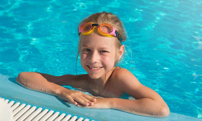 young girl swimmer resting against side of pool