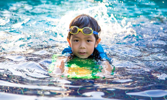young swim goggles boy racing through pool