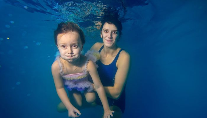 young woman and girl holding breath underwater in pool