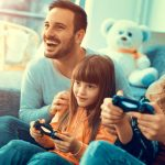 young family excitedly playing video game