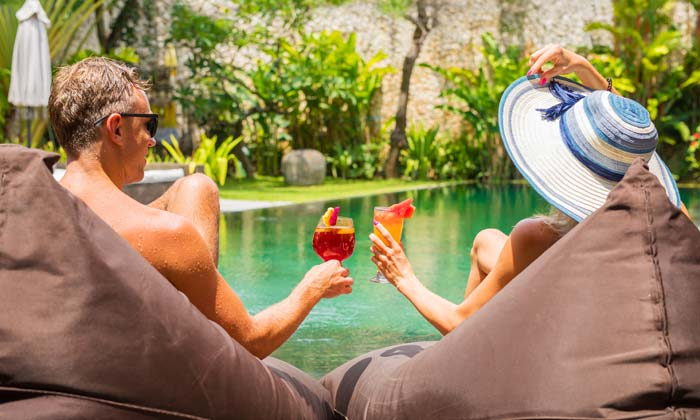 man and woman relaxing by pool drinking