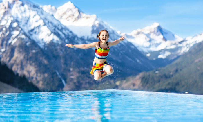 young girl jumping into pool with mountains in background