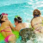 three kids enjoying time in pool water