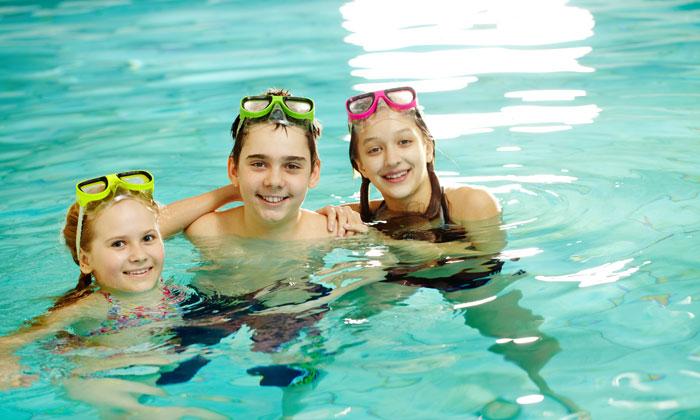 three kids having fun in pool water