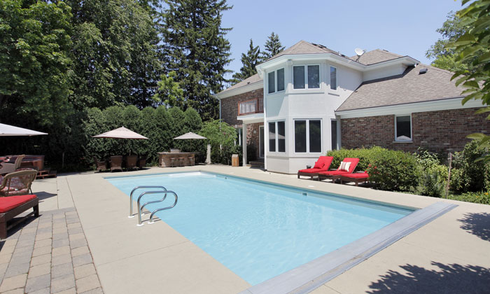 backyard inground pool with chairs for seating