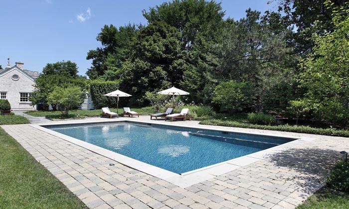 backyard rectangular pool with relaxing chairs